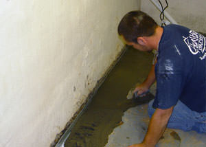 Restoring a concrete slab floor with fresh concrete after jackhammering it and installing a drain system in Madison.